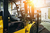 Close up of Forklift Truck inside warehouse or factory or logistics company, sunlight effect
