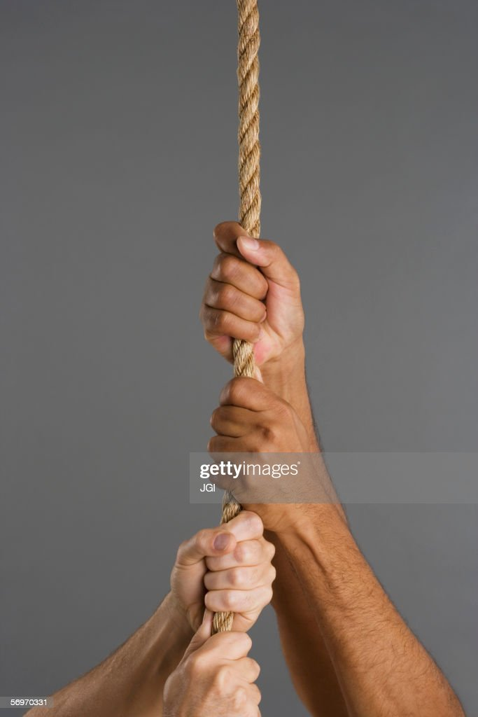 Close up of four hands hanging on rope