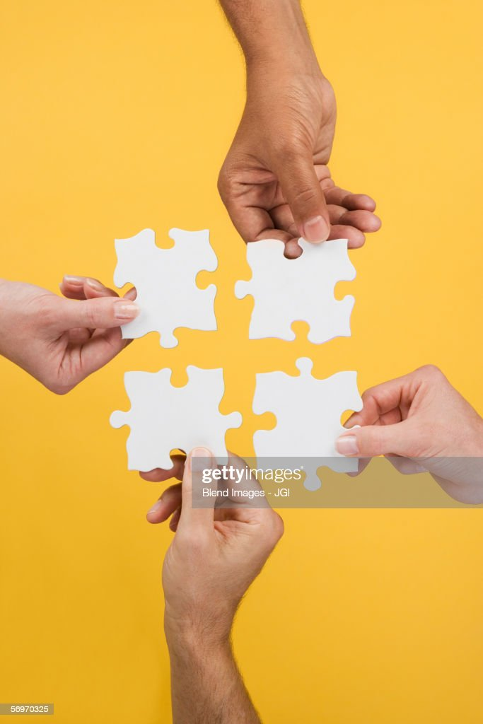 Close up of four hands holding puzzle pieces : Stock Photo