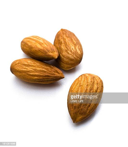 A close up of four whole almonds on a white background