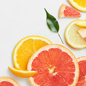 Close up of fresh citrus slices with leaf on white background