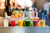 Close up color image depicting freshly made fruit juices and smoothies on display in a row and for sale at a food and drink market in London, UK. Selective focus on the plastic cups containing the fre