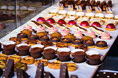 Close up vertical color image depicting a selection of freshly baked delicious cakes and cupcakes for sale at Borough Market in London, one of the oldest and most popular food markets in the world. Ro