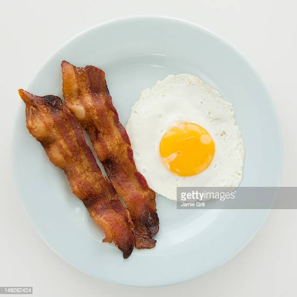 Close up of fried egg with bacon, studio shot