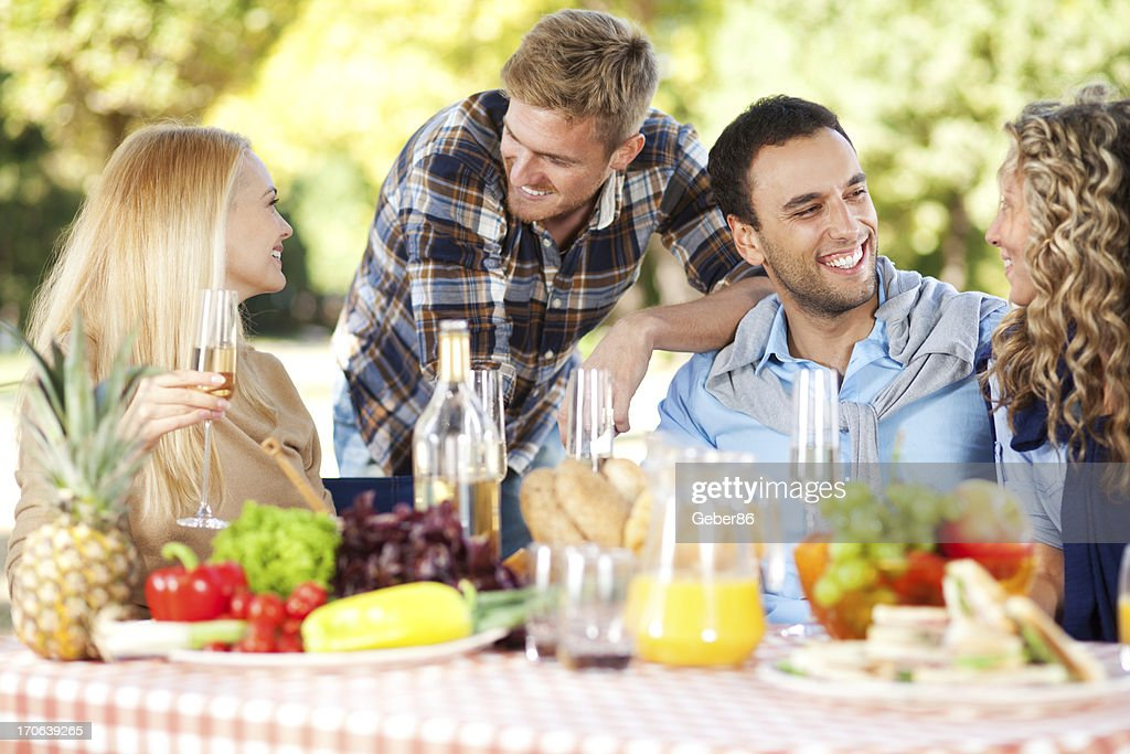 Close up of friends having picnic in park : Stock Photo
