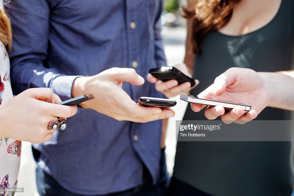 Close up of friends using smart phones.