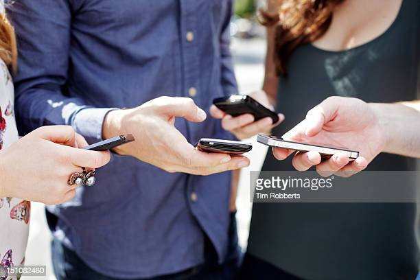 Close up of friends using smart phones.
