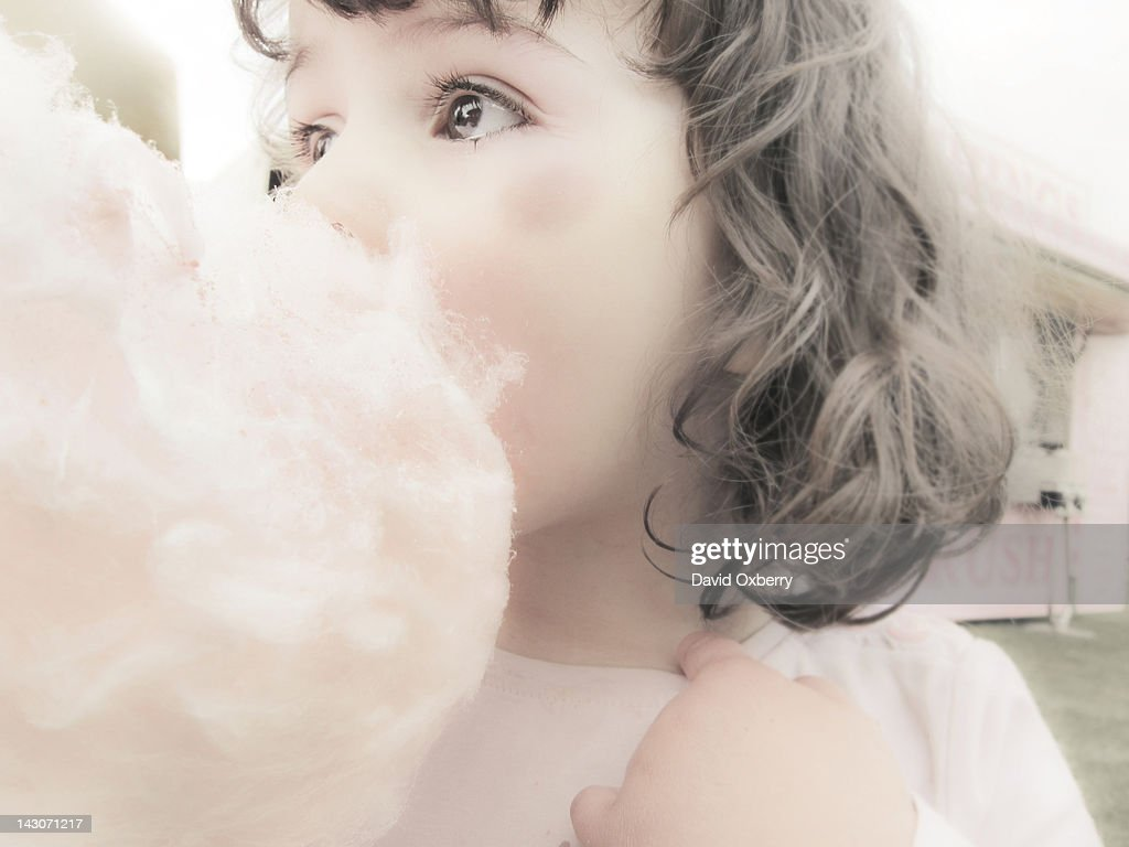 Close up of girl eating cotton candy