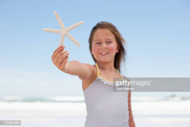 Close up of girl holding starfish