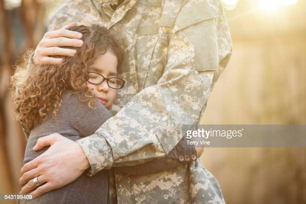 Close up of girl hugging soldier father