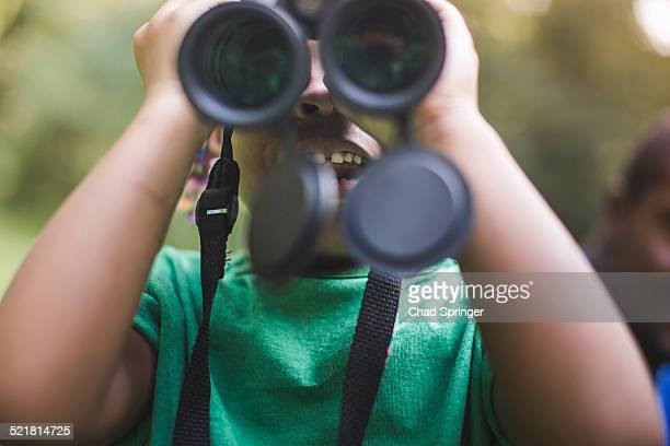 Close up of girl looking through binoculars in forest eco camp