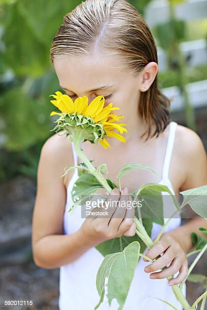 Close up of girl smelling sunflower outdoors