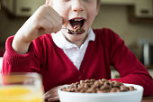 Close Up Of Girl Wearing School Uniform Eating Bowl Of Sugary Breakfast Cereal In Kitchen