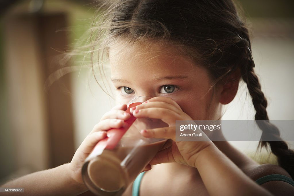 Close up of girl with braids drinking chocolate milk : Stock Photo