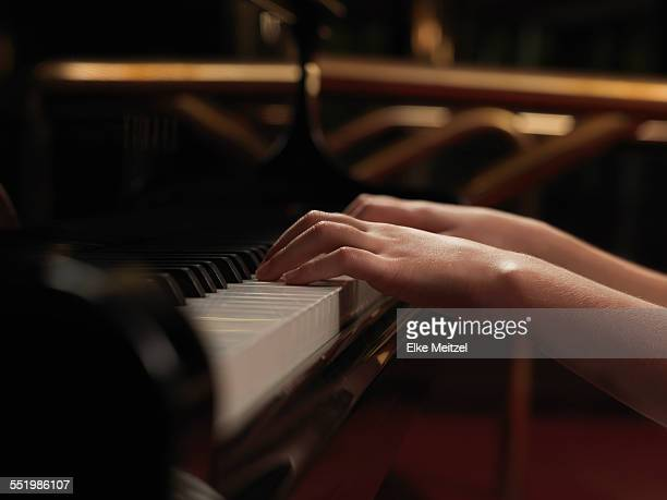 Close up of girls hands playing piano keys