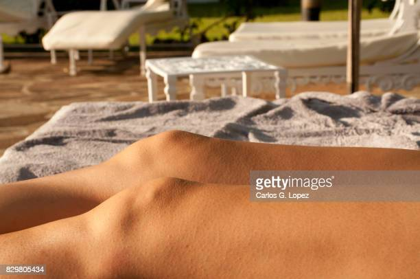 Close up of girl's legs sunbathing near pool