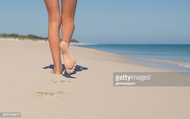 Close up of girl's legs walking on the beach