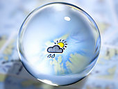 Close up of glass ball with rain cloud and sun in center