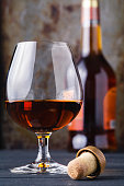 Close up of glass cognac or whiskey on rusty background