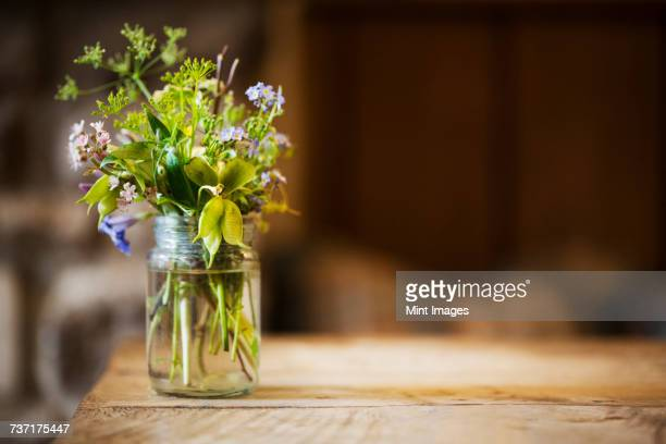 Close up of glass jar with small bunch of wild flowers on a wooden table.