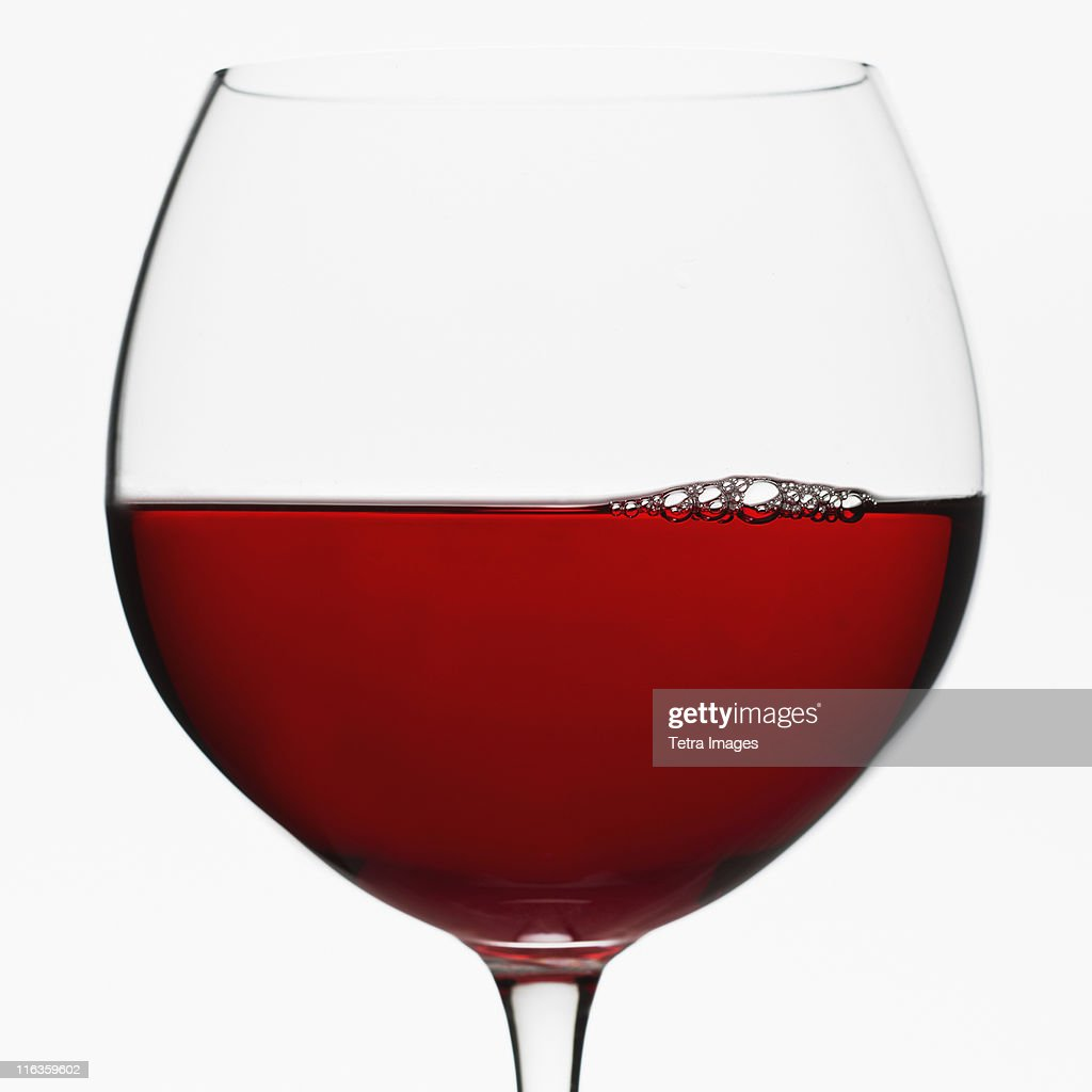 Close up of glass of red wine on white background