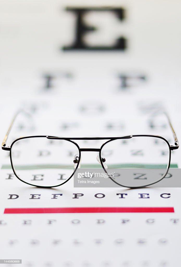 Close up of glasses on eye chart,  studio shot