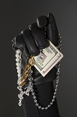Close up of gloved hand with money and jewels