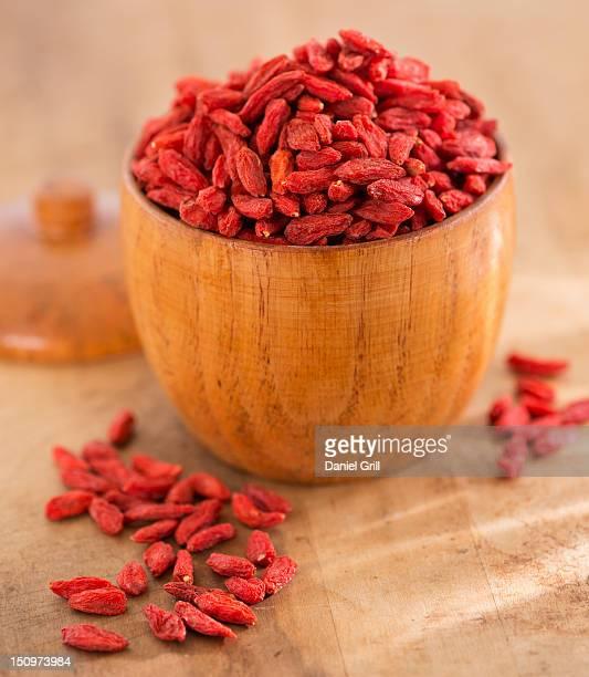 Close up of goji berries in wooden bowl, studio shot