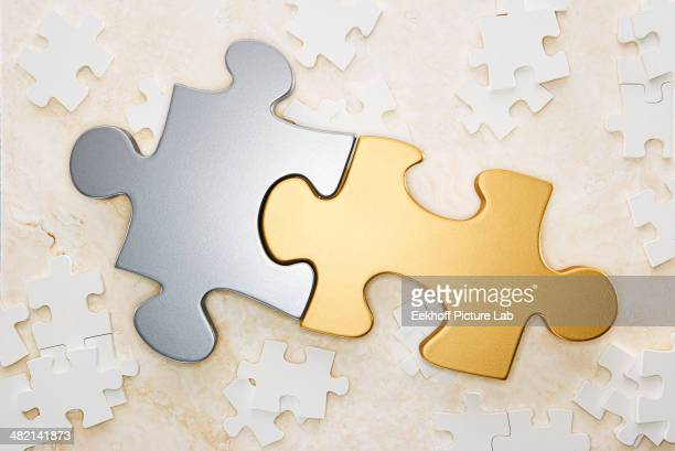 Close up of gold and silver puzzle pieces