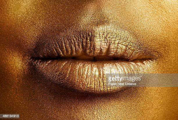 Close up of golden painted lips on gold skin
