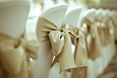 Close up of golden ribbon tied white chair in luxury dinner party with vintage color style.
