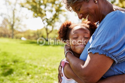 Close Up Of Granddaughter Hugging Grandmother In Park : Stock Photo