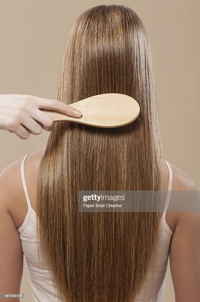 Close up of hair brushing straight brown hair