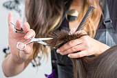 close up of a hairdressers hands cutting wet hair in a hair salon.