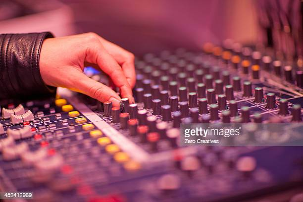 Close up of hand and mixing desk in recording studio