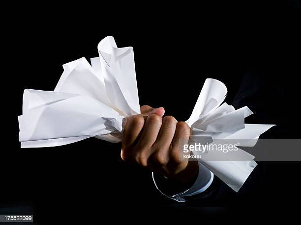 Close up of hand crushing a paper