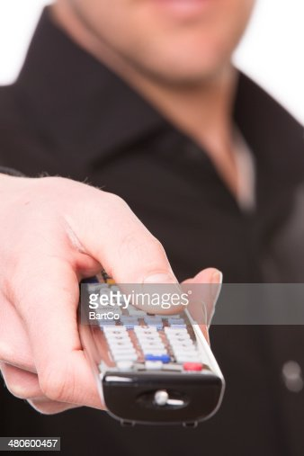 Close up of hand holding a remote control : Stock Photo