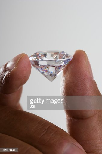 Close up of hand holding diamond : Stock Photo