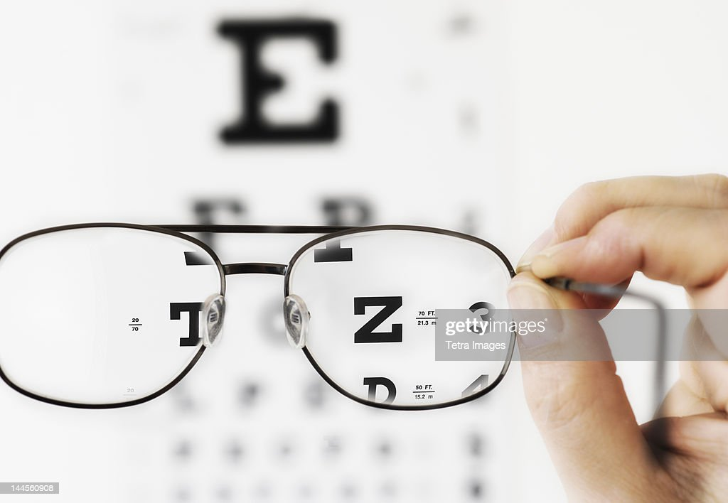 Close up of hand holding glasses above eye chart, studio shot
