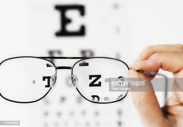 Close up of hand holding glasses above eye chart, studio shot