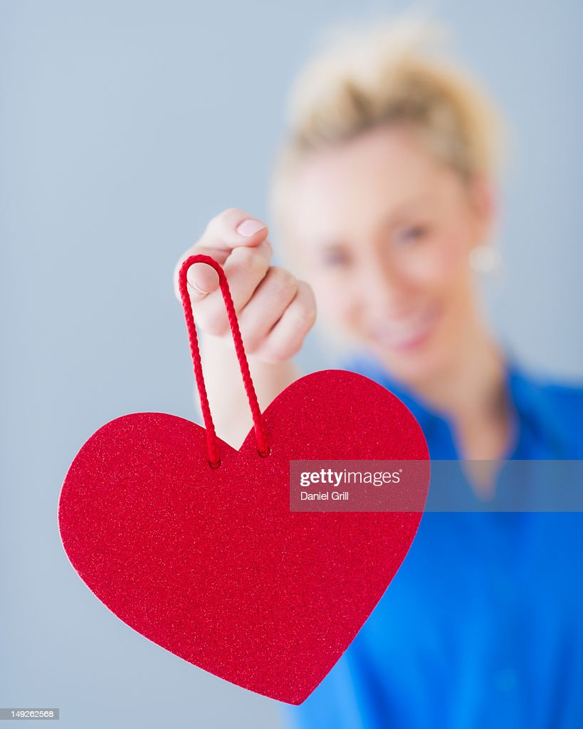 Close up of hand of young woman holding red heart, studio shot : Stock Photo