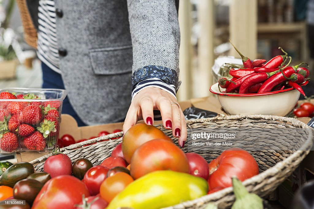 Close up of hand picking tomato from basket. : Stock Photo