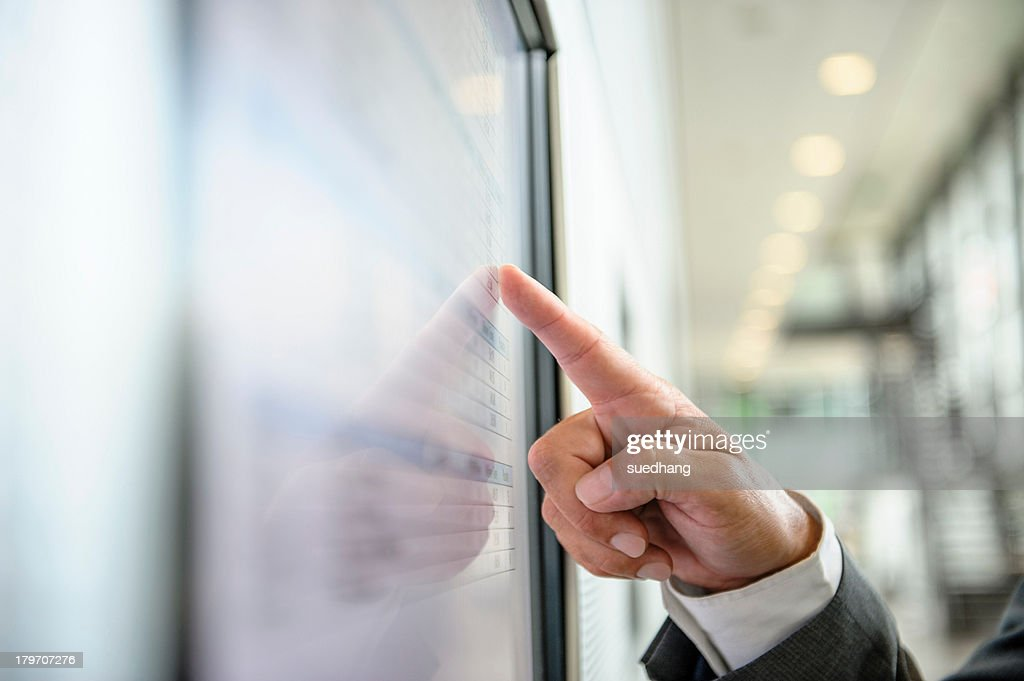 Close up of hand pointing at wall screen : Stock Photo