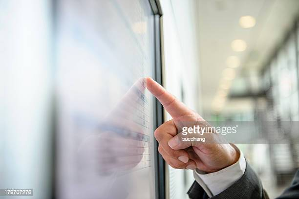 Close up of hand pointing at wall screen