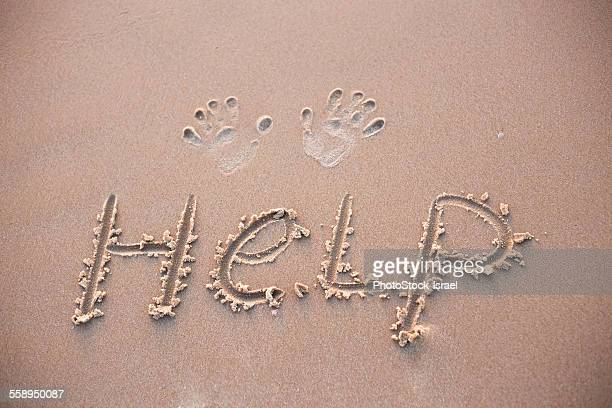 Close up of hand prints and word help written in sand