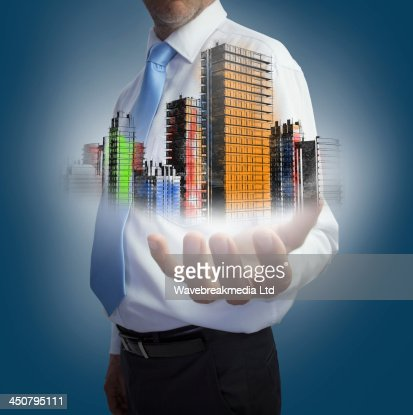 Close up of hand showing colored holographic city : Stock Photo