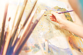 Creativity has no boundaries. Selective focus on a hand of an artist holding a painting brush and creating a new abstract masterpiece on an art canvas.