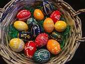 close up of handmade colorful eastereggs in a green nest, holiday