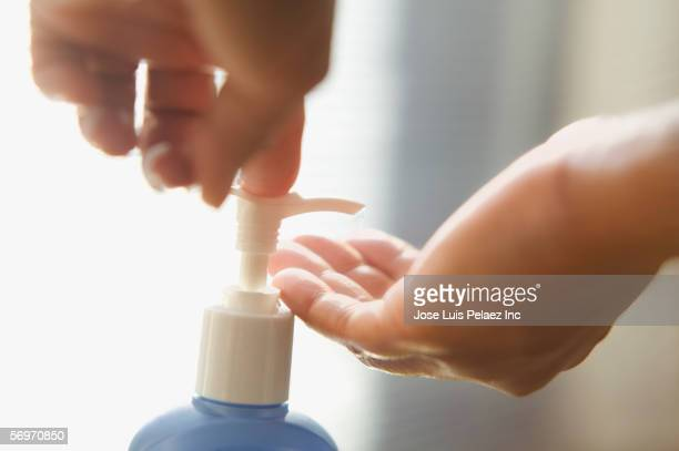 Close up of hands applying lotion