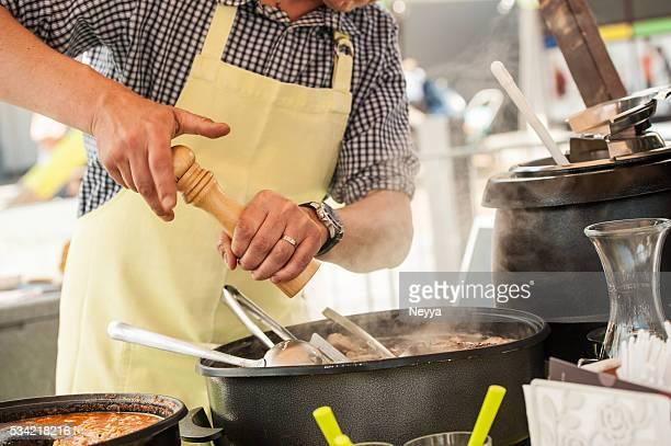 close up of hands cooking at street market
